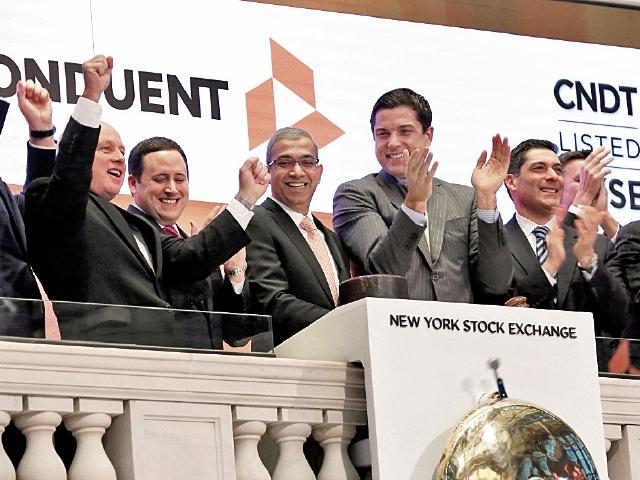 Ashok Vemuri (der.) CEO de Conduent celebra junto a otros directivos el ingreso a la bolsa de valores de Conduent. (Foto Prensa Libre: AP)
