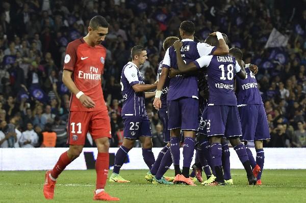 Los jugadores del Toulouse celebran, mientras Ángel Di María camina decepcionado por la derrota del PSG. (Foto Prensa Libre: AFP)