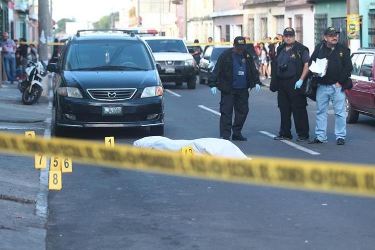 El cuerpo de Santizo quedó en la calle, mientras investigadores inspeccionan la escena. (Foto Prensa Libre: Álvaro Interiano)