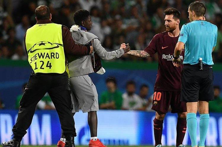 La seguridad se encargó de sacar del campo al aficionado, no si antes estrechar la mano de su ídolo. (Foto Prensa Libre: AFP)