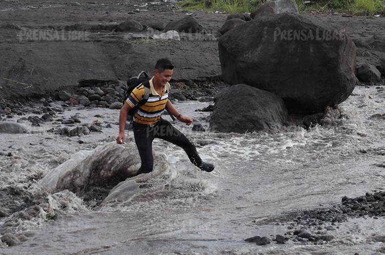 Un vecino cruza una correntada que formó una zanja de casi cinco metros de profundidad en el camino. (Foto Prensa Libre: Esbin García)