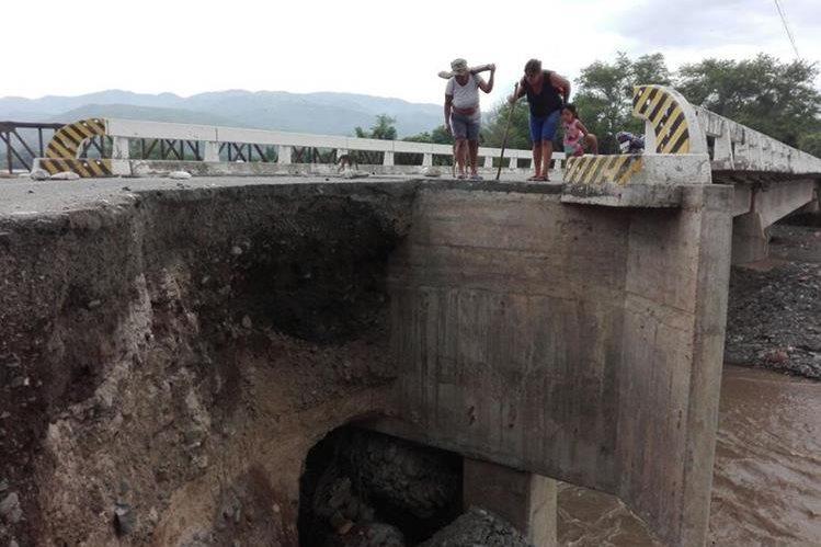 Vecinos observan los daños en uno de los extremos del puente El Tambor que se halla en el kilómetro 109 de la ruta entre El Jicaro, El Progreso y Cabañas, Zacapa. (Foto Prensa Libre: Hugo Oliva)