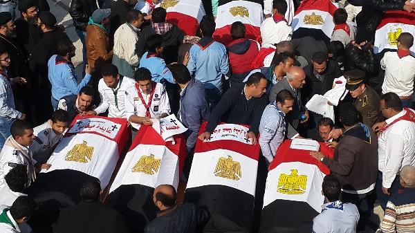 Funcionarios egipcios acompañan a los ataúdes de las víctimas del atentado. (AFP).