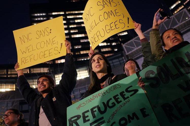 Activistas portan pancartas en apoyo a los refugiados sirios e iraquíes. (Foto Prensa Libre: AFP).