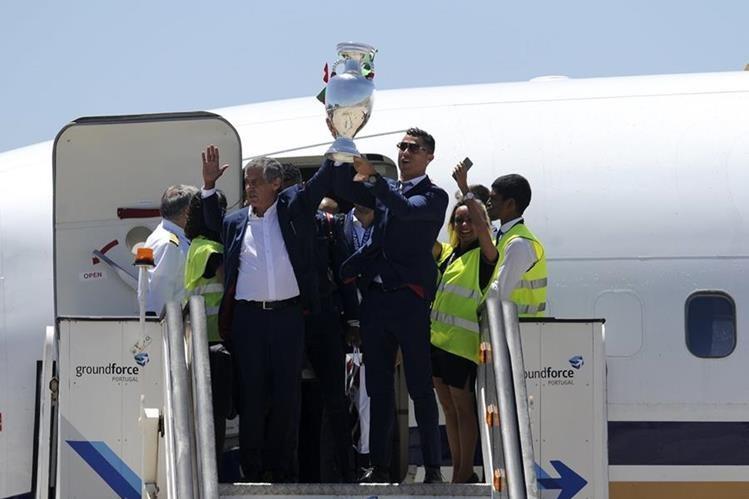 La estrella portuguesa Cristiano Ronaldo levanta el trofeo de la Eurocopa antes de abordar el vuelo que trasladó a la selección a territorio luso. (Foto Prensa Libre: AFP)