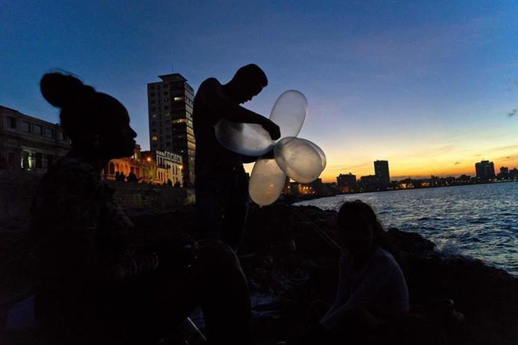 El cubano Junior Torres López une condones inflados para que su línea de pesca mantenga su cebo en el agua y aumente la resistencia contra la atracción de pescado pesado. (Foto Prensa Libre: AP).