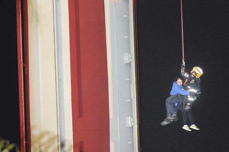 Un socorrista ayuda a descender a una mujer de la atracción. (Foto Prensa Libre: AP).