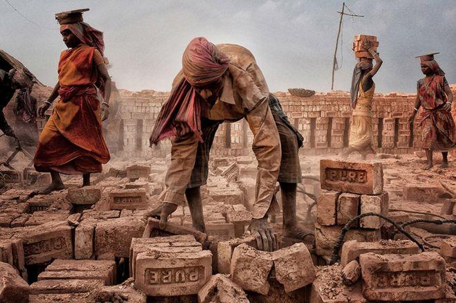 """""""En esta foto, hombres y mujeres están trabajando duro para alimentar a cada una de sus familias"""", cuenta Shibasish Saha, la fotógrafa. """"Las mujeres olvidan su dolor y trabajan junto a los hombres en un campo de ladrillos"""". La tomó en Bengala Occidental, en India. SHIBASISH SAHA"""