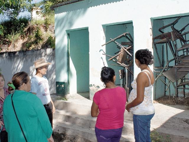 Integrantes del  comité de padres de familia observan el mal estado en que se hallan los servicios sanitarios. (Foto Prensa Libre: Héctor Contreras)
