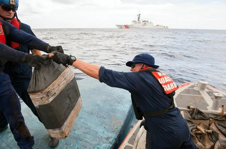 In this July 19, 2015 photo released by the U.S. Coast Guard, a Coast Guard Cutter Stratton boarding team seizes cocaine bales from a self-propelled semi-submersible in international waters off the coast of Central America. The seizure of around 12,000 pounds was one of the largest busts of its kind. (Petty Officer 2nd Class LaNola Stone/U.S. Coast Guard via AP)