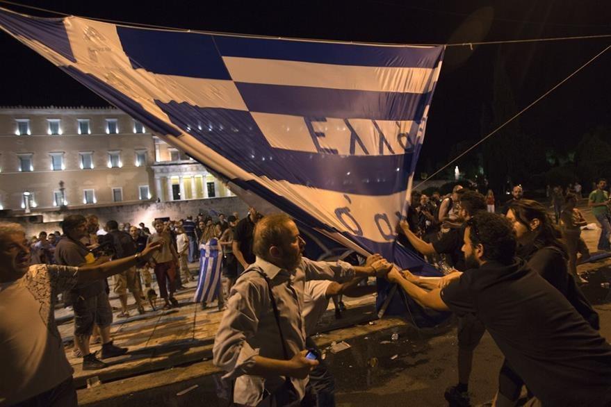 Manifestantes portan la bandera de Grecia durante la jornada de protestas en contra del acuerdo que plantea el Gobierno. (Foto Prensa Libre: AP).