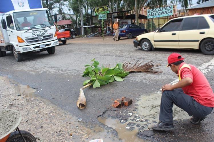 Empleado de una gasolinera hecha cemento en un bache en el km 116.5 de la ruta Interamericana, en Jutiapa. (Foto Prensa Libre: Óscar González)