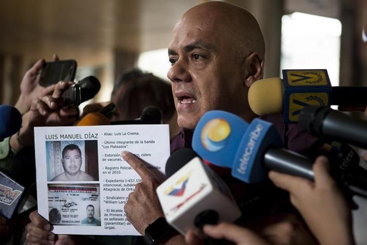 El jefe de campaña del chavismo, Jorge Rodríguez, muestra una imagen del opositor asesinado. (Foto Prensa Libre: EFE).