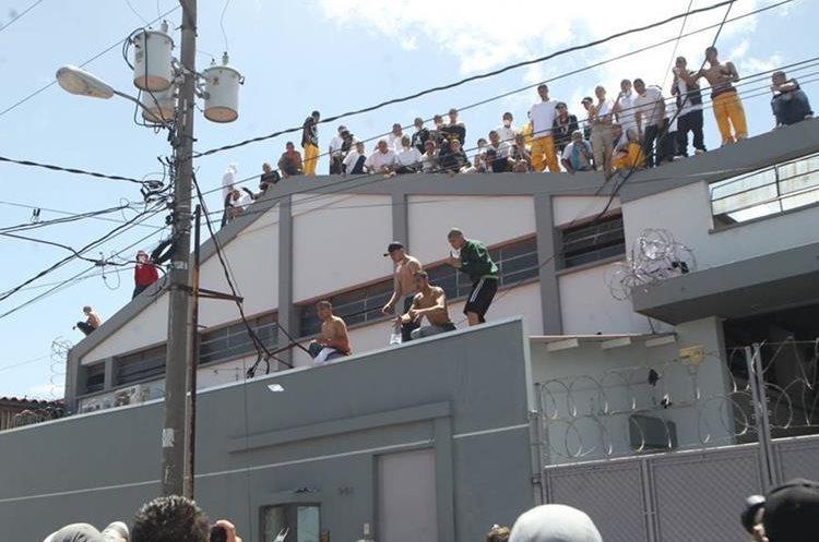 Los internos se subieron a los techos de los inmuebles aledaños al correccional. (Foto Prensa Libre: Estuardo Paredes)