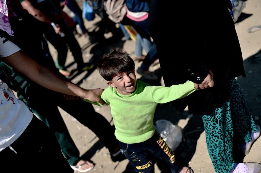 Un niño llora, mientra espera con su familia transporte en la frontera entre Grecia y Macedonia. (Foto Prensa Libre: AFP).