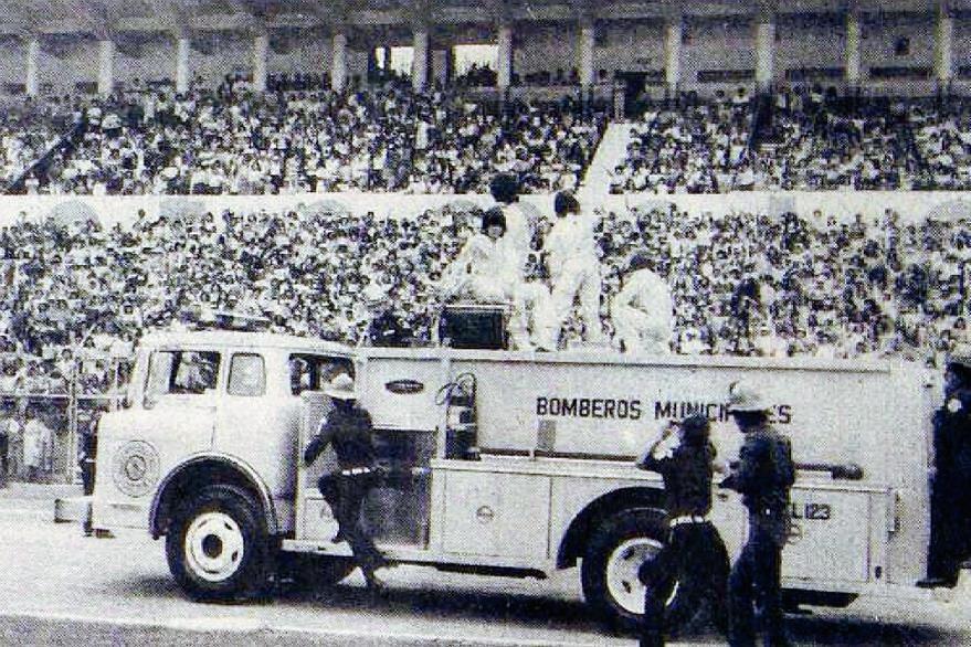 Ante la ovación de más de 30,000 admiradores, Los Chicos saludan levantando las manos cuando iban abordo de una motobomba de los bomberos municipales. (Foto Prensa Libre: Hemeroteca)