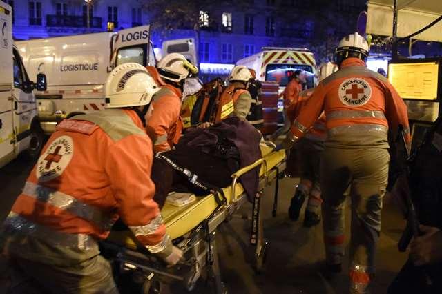 Integrantes de la Cruz Roja evacuan a uno de los heridos en Paris, Francia. (Foto Prensa Libre: AFP)