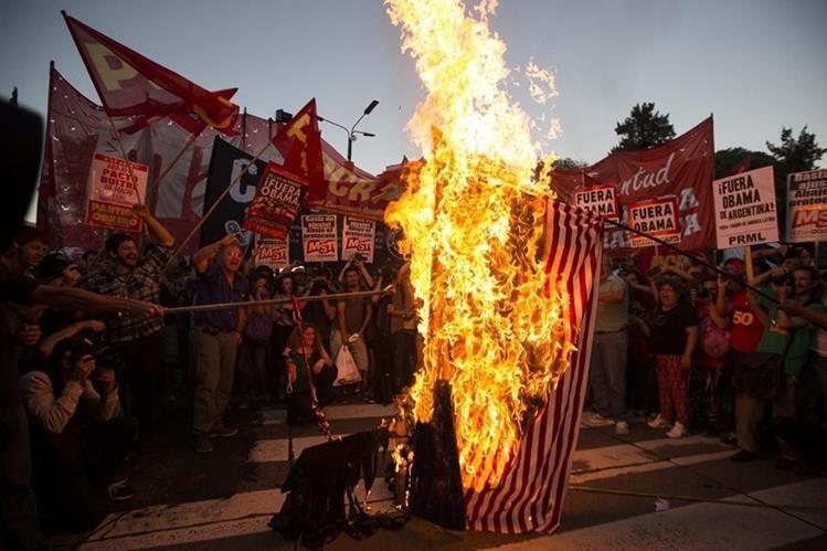Manifestantes queman una bandera de EE. UU. frente a la embajada de Wasihington en Buenos Aires. (Foto Prensa Libre: AP).