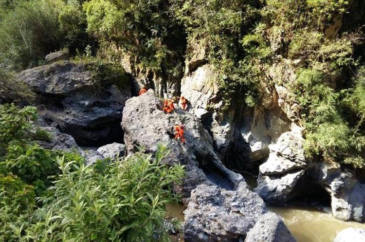 Con equipo especial, bomberos Voluntarios buscan entre rocas a un hombre que cayó con su vehículo al Río Selegua. (Foto Prensa Libre: Mike Castillo)