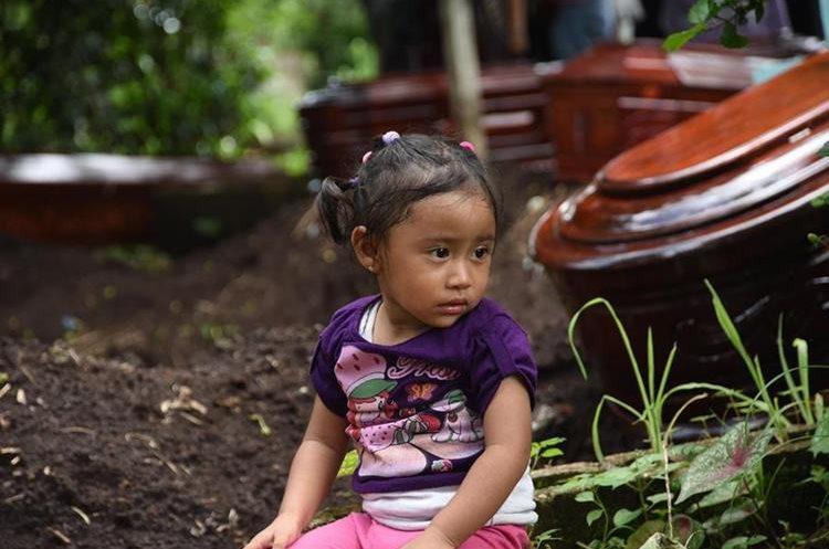 Niña se sienta cerca de los ataúdes de cinco víctimas del Volcán de Fuego que fueron inhumadas. (Foto Prensa Libre: AFP)
