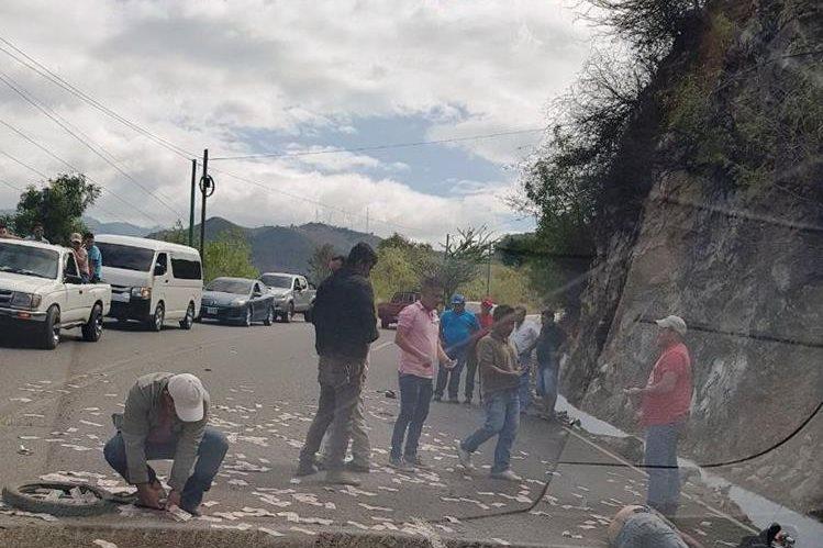 Vecinos del lugar recogieron el dinero del motorista que fue atropellado.(Foto Prensa Libre: Mario Morales)