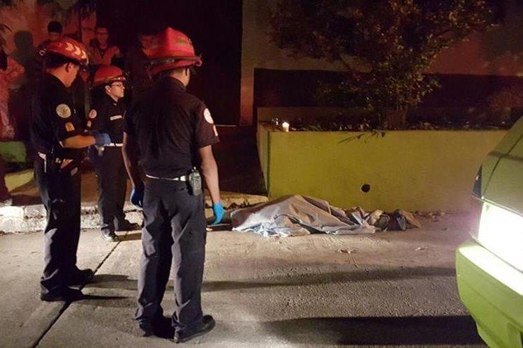 Bomberos Municipales cubren el cuerpo del hombre acribillado en la zona 12. (Foto Prensa Libre: Cortesía)