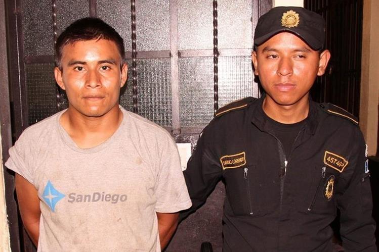 Mario Canteo Iquic es resguardado por un agente de la PNC en Siquinalá, Escuintla. (Foto Prensa Libre: PNC)
