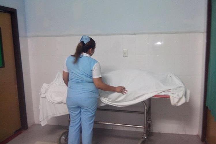 Enfermera cubre con una sábana el cuerpo sin vida de Héctor Leiva López. (Foto Prensa Libre: Hugo Oliva)