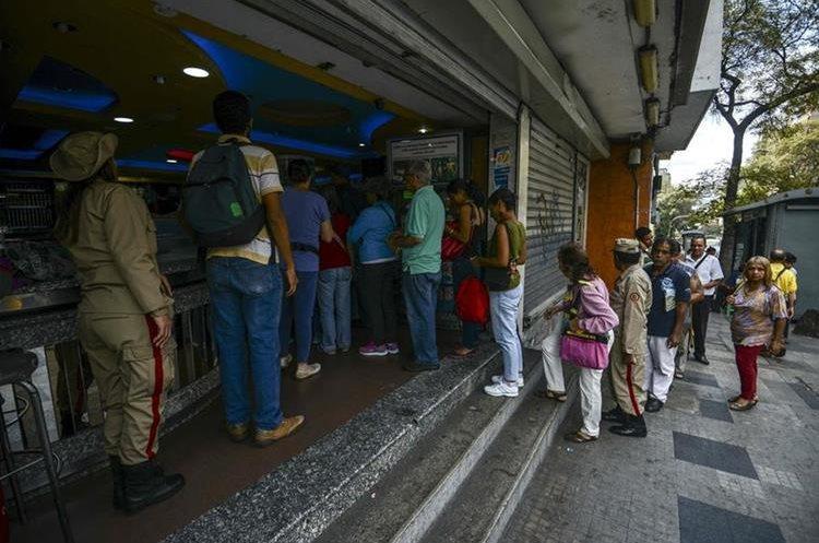 Miembros de la Guardia Bolivariana vigilan venta de pan en una pastelería de Caracas. (Foto Prensa Libre: AFP)
