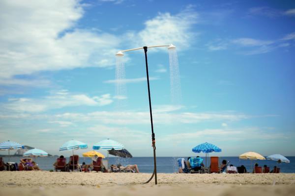 Una ducha de manera permanente está disponible con agua para los visitantes a la playa de Copacabana, Brasil, sin embargo la sequía amenaza con limitar esos recursos para los brasileños. (Foto Prensa Libre: AP).