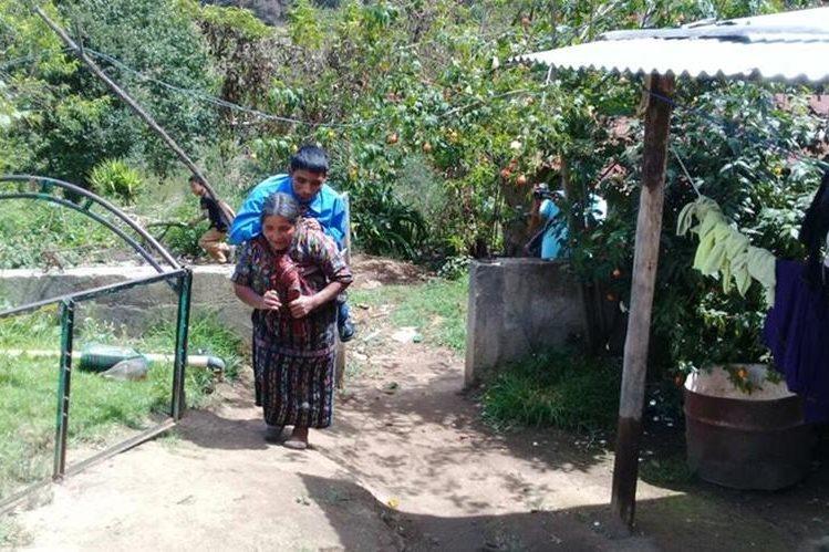 Juana Chiroy carga su hijo Carlos Cuxulic, de 41 años, quien padece de parálisis en las piernas. (Foto Prensa Libre: Ángel Julajuj)