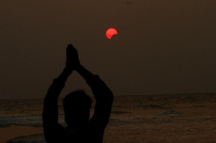 An Indian fisherman prays to a partial solar eclipse seen in the sky over Bay of Bengal in Konark, 60 kilometers (37 miles) from eastern Indian city Bhubaneswar, India, Wednesday, March 9, 2016. (AP Photo/Biswaranjan Rout)