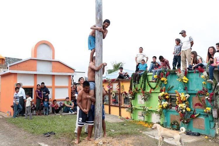 Algunos de los participantes del juego del palo encebado tratan de alcanzar los Q500 de premio. (Foto Prensa Libre: Eduardo Sam Chun)