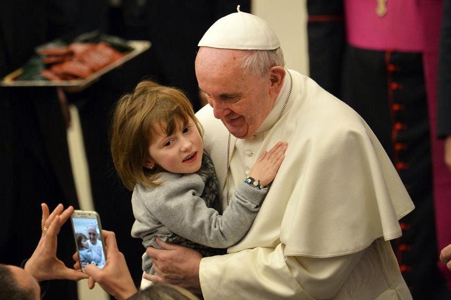 El papa Francisco sostiene a un niño durante la audiencia general. (Foto Prensa Libre: AFP).