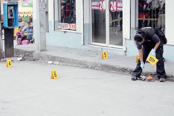 Peritos del Ministerio Públic recogen casquillos de bala en el lugar en el que fueron baleados los ayudantes de buses. (Foto Prensa Libre: Erick Ávila)