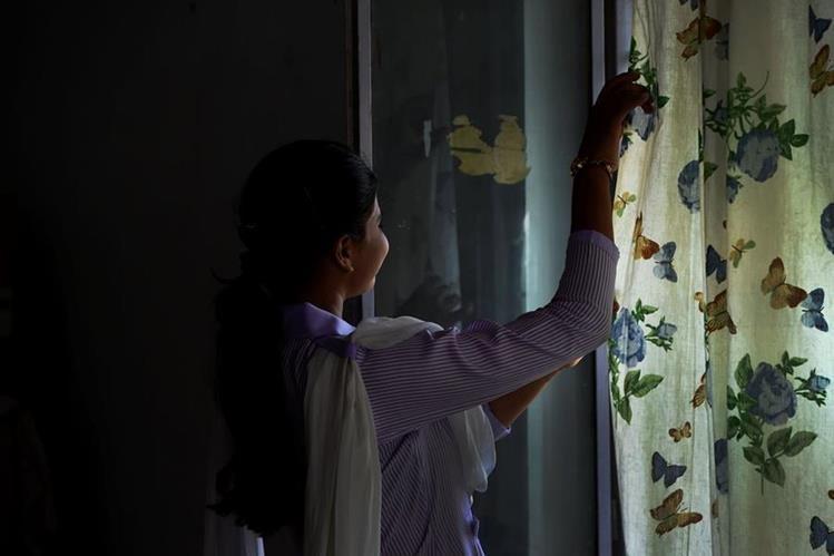 Esham Masih, hija de Asia Bibi, observa a través de la ventana en su vivienda en Lahore. (Foto Prensa Libre: AFP).