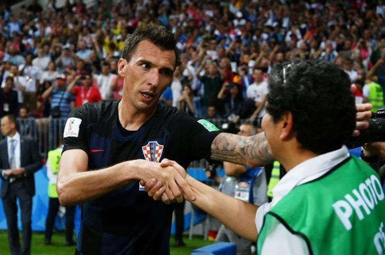 El delantero de Croacia, Mario Mandzukic le ofrece disculpas al fotógrafo salvadoreño. (Foto Prensa Libre: Twitter)