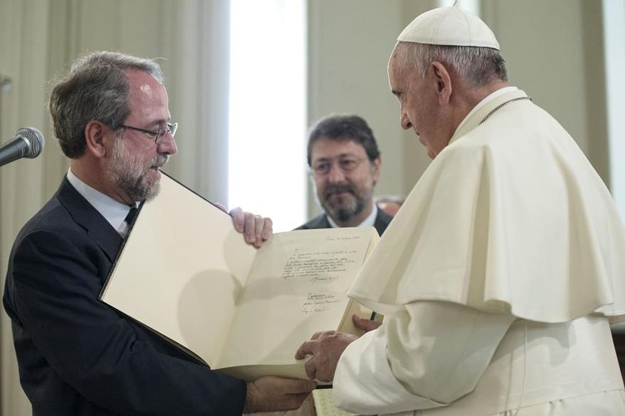 El papa Francisco (derecha), sostiene un libro que le entregó, Eugenio Bernardini, representante de la iglesia Valdense a donde un pontífice nunca había llegado. (Foto Prensa Libre: AFP).