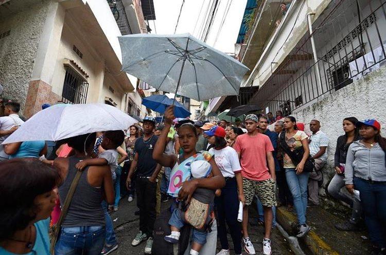 Sin importar las condiciones climáticas, los venezolanos han salido a las urnas desde las primeras horas de la mañana. (Foto Prensa Libre: AFP)