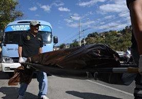Forense lleva el cadáver de un estudiante asesinado por pandilleros en un autobús en Tegucigalpa.(Foto Prensa Libre:AFP).