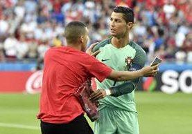 Cristiano Ronaldo fue seguido en el juego de ayer contra Gales por un voluntario en el estadio. (Foto Prensa Libre: AP)