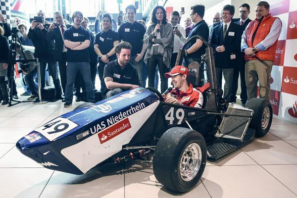 Sebastian Vettel, de Ferrari, a bordo de un coche de carreras diseñado por estudiantes de la Universidad de Niederrhein. (Foto Prensa Libre: EFE)