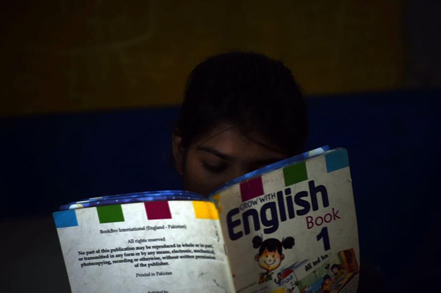 Esha Masih, hija de Asia Bibi, lee un libro en una escuela de Lahore, Pakistán. (Foto Prensa Libre: AFP).