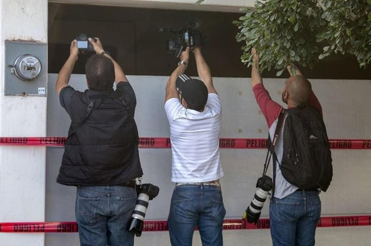 """Photographers take pictures and film the house where five gang suspects were killed in the military operation which resulted in the recapture of Joaquin """"El Chapo"""" Guzman on January 8 in the city of Los Mochis, Sinaloa State, Mexico, on January 10, 2016. Mexican marines recaptured fugitive drug kingpin Joaquin """"El Chapo"""" Guzman on January 8 in the northwest of the country, six months after his spectacular prison break embarrassed authorities. AFP PHOTO/HECTOR GUERRERO"""