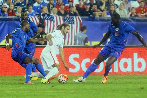 Brad Evans de EE.UU. disputa el balón con jugadores de Haití. (Foto Prensa Libre: AFP)
