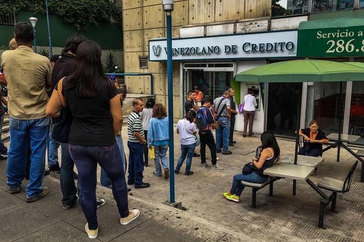 Miles de Venezolanos deben hacer filas porque la falta de efectivo también afecta a la población. (Foto Prensa Libre: EFE)