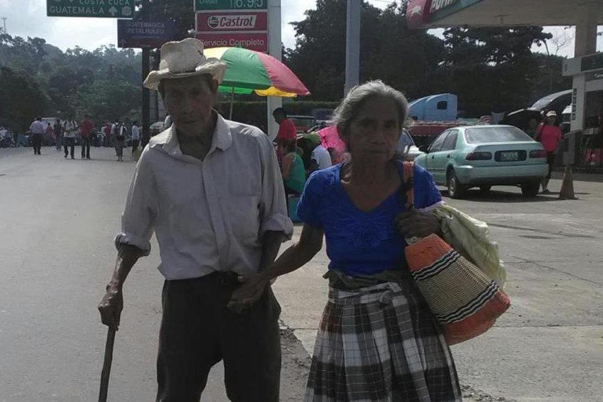 Una pareja de ancianos camina debido al bloqueo en el km 212 de la ruta al suroccidente, en Colomba, Quetzaltenango. (Foto Prensa Libre: Alexánder Coyoy)