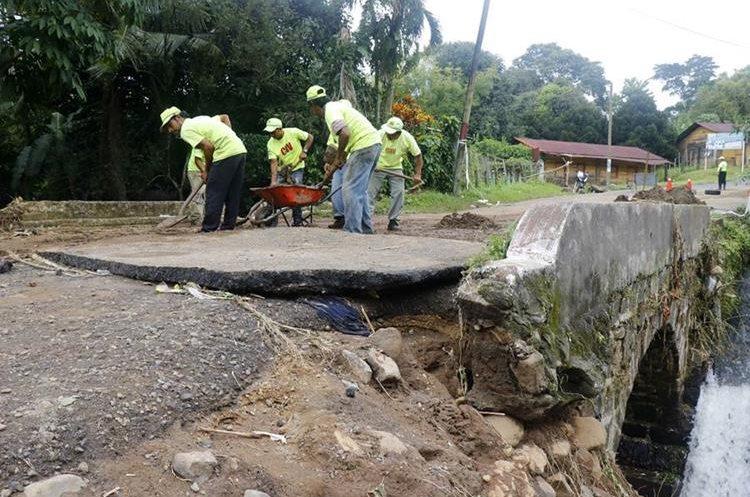 Empleados de Covial hacen trabajos de mitigación en uno de los puentes que quedó con daños parciales en San Martín Zapotitlán.(Foto Prensa Libre: Rolando Miranda)