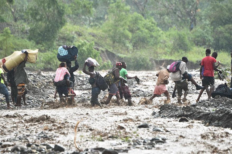 """Hombres y mujeres tratan de cruzar un río crecido por las lluvias que llevó a Haití el huracán """"Matthew"""". (Foto Prensa Libre: AFP)."""