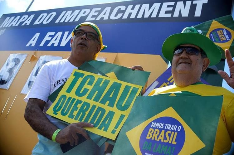 """Activists hold a sign reading """"Bye Darling"""" duringa demo in support of the impeachment of Brazilian President Dilma Rousseff in front of the National Congress in Brasilia, on April 17, 2016.  Rousseff risks being driven from office if the lower house votes in favor of an impeachment trial Sunday. / AFP PHOTO / ANDRESSA ANHOLETE"""